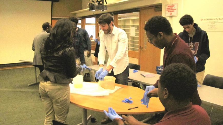 Matt Best shows students rhesus and human monkey brains.