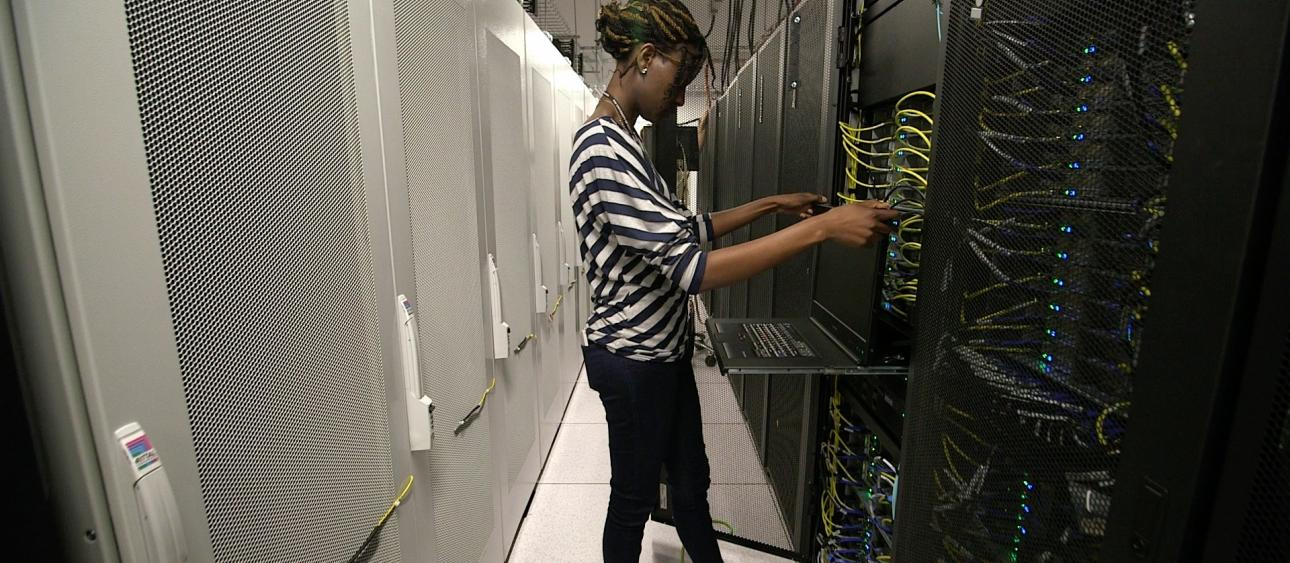 Research Computing Center system administrator Hellen Nyatsambo puts finishing touches on the Midway2 high-performance computing cluster. Photo by UChicago Creative staff.